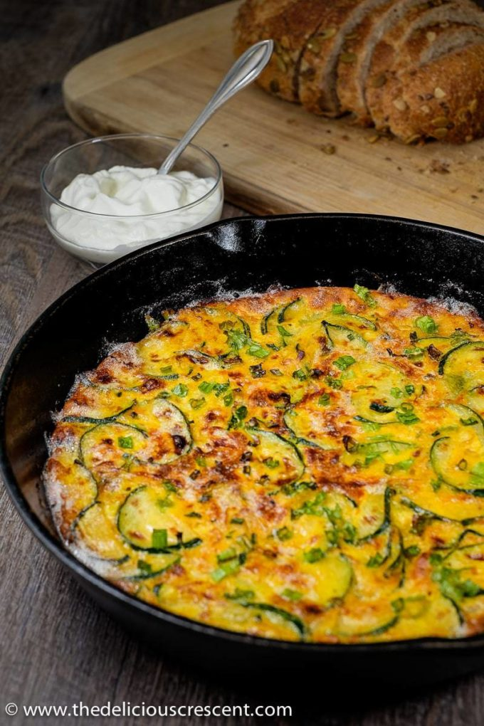 Persian zucchini frittata baked in a cast iron skillet and placed on a table.