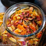 Homemade tea blend made with rose, citrus, berry, apple and stored in a glass bottle.
