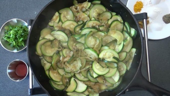 Zucchini being sauteed to prepare kuku kadoo.