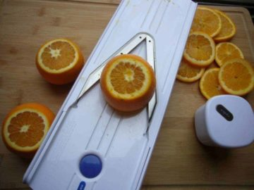 Oranges being sliced using a mandolin slicer to be dried for making a homemade tea blend.