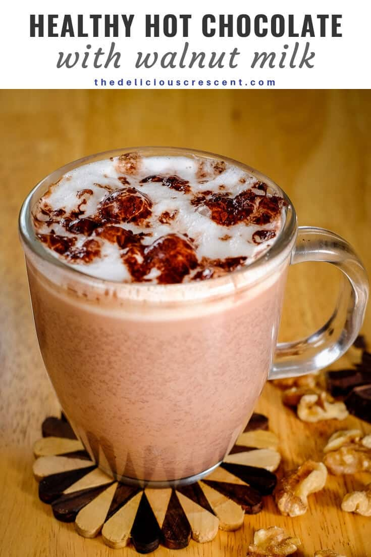 Steaming hot chocolate made with walnut milk in a glass mug with foamy milk and cocoa on the top.