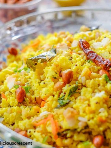 Lemon cauliflower rice seasoned with spices, herbs, chilies and served in a glass plate.