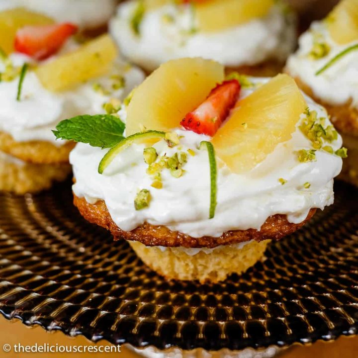 Pineapple cupcakes with fresh cream placed on a cake stand.