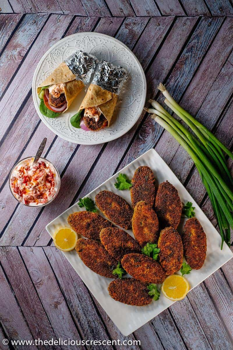 Overhead view of spicy fish cakes (shami kabab) served on the table with wraps.