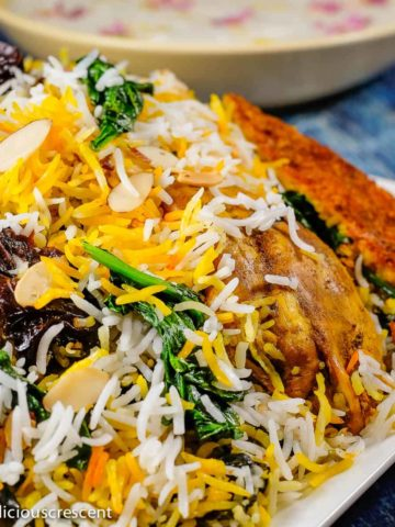 Persian saffron rice with chicken, yogurt and spinach served in a plate.