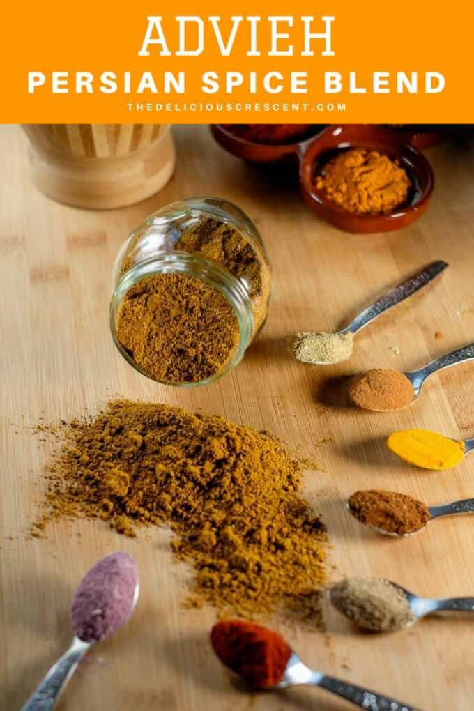 A bottle of Persian spice mix with the spice powders in spoons arranged around it.
