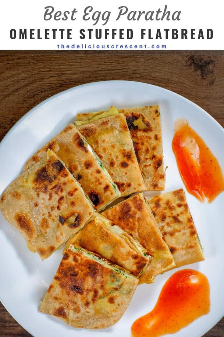 Egg Paratha or anda paratha is an omelette stuffed and layered flat bread. It is a traditional Indian breakfast that is made with whole grain wheat flour and provides high quality protein and good fiber. This popular recipe shows step by step how to make this famous Indian bread, but cooking with just adequate amount of oil, and with very tasty results. #flatbread #Indianrecipe #thedeliciouscrescent