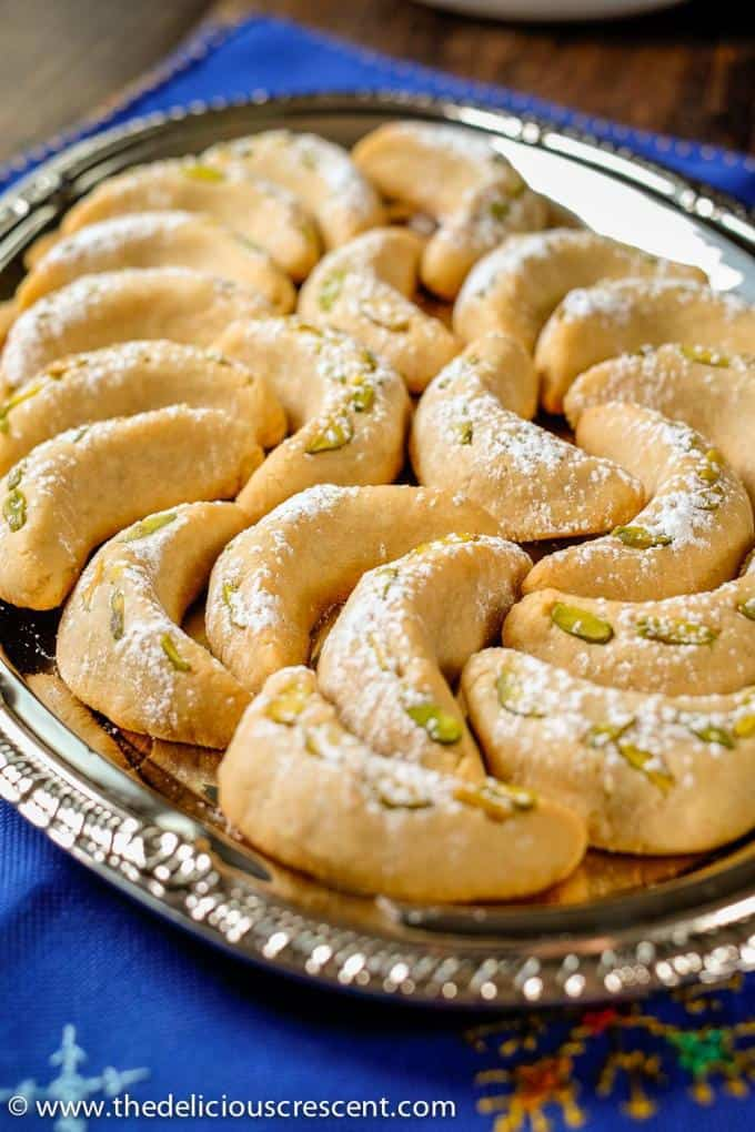 Vanilla crescent cookies (vanillekipferl) arranged on a steel plate and placed on a blue table mat.