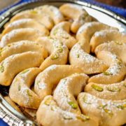 Vanilla crescent cookies dusted with vanilla sugar and arranged on a plate.
