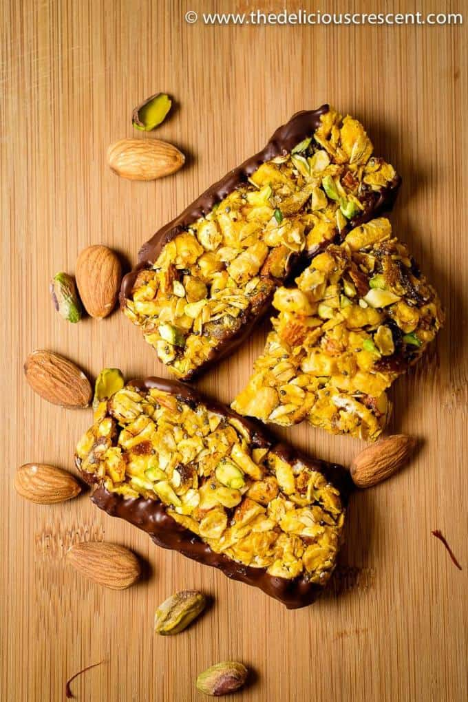 Three almond granola bars placed on a wooden board with a few almonds around.