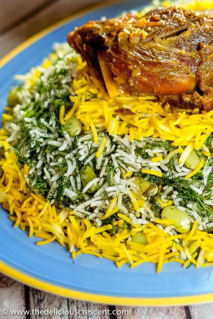 Amazing Baghali polo (dill rice with lima beans) arranged on a serving plate with a lamb shank.