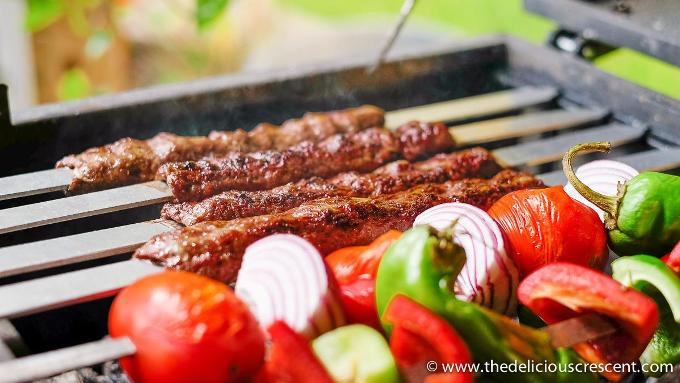 Distant view of the kabob koobideh skewers on a grill with other vegetables on the side.