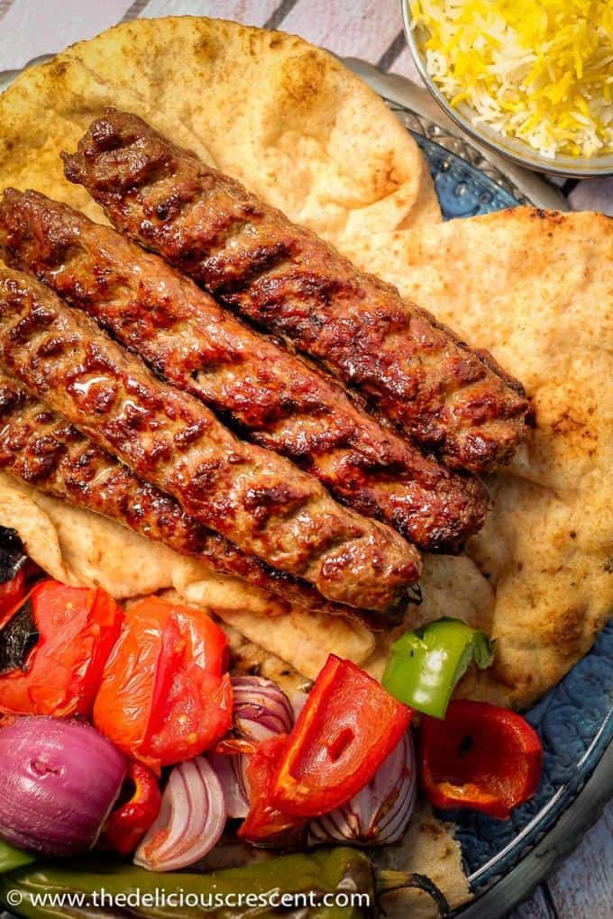 Overhead view of koobideh kabob skewers with vegetables all placed on flat breads.