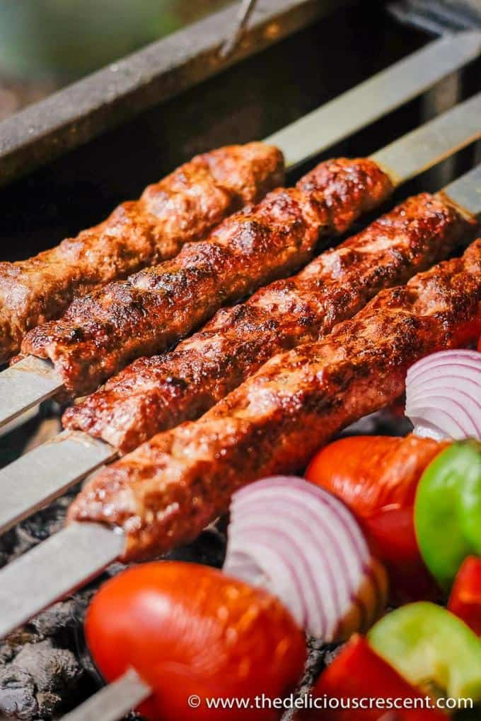 Koobideh kabob skewers with vegetables on skewers, all placed on a grill.