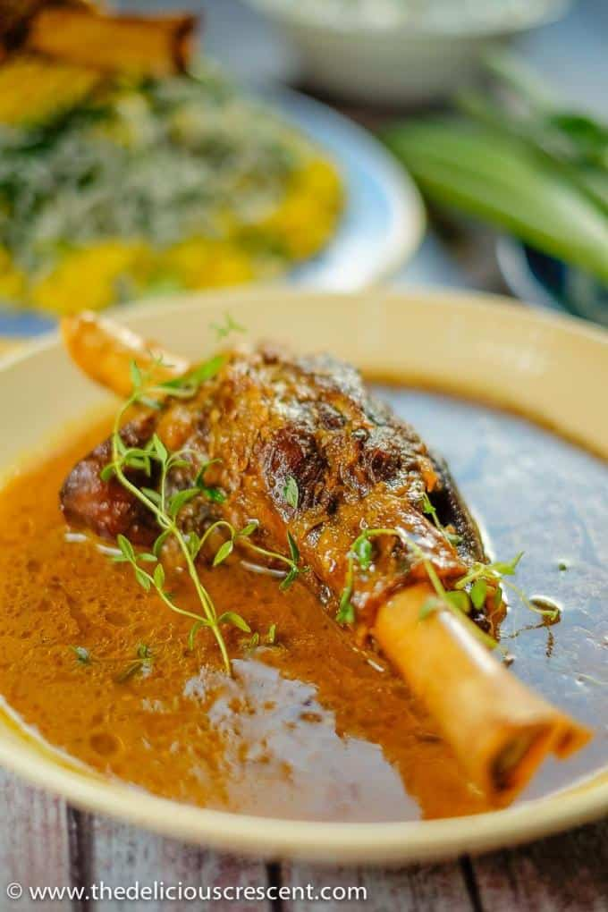 Persian braised lamb shanks served in a round serving dish with a fantastic sauce.