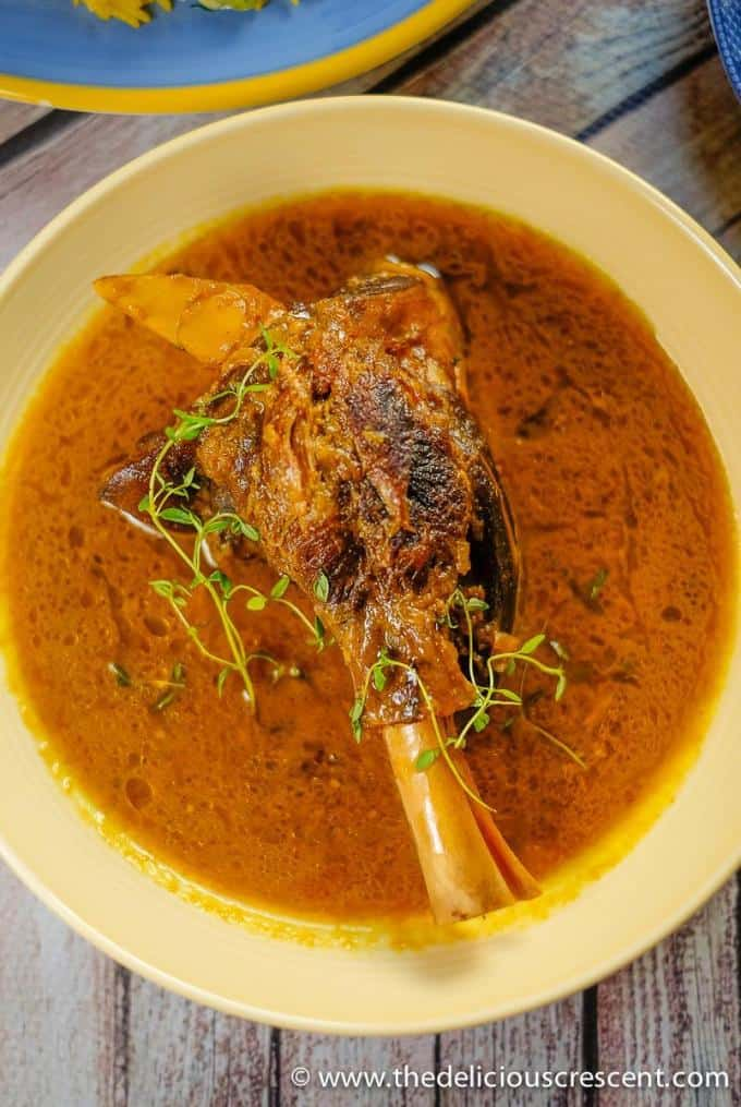 Overhead view of lamb shanks with a fragrant Persian spiced sauce.