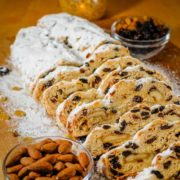 Classic German stollen dusted with powdered sugar, sliced and served on a wooden board.