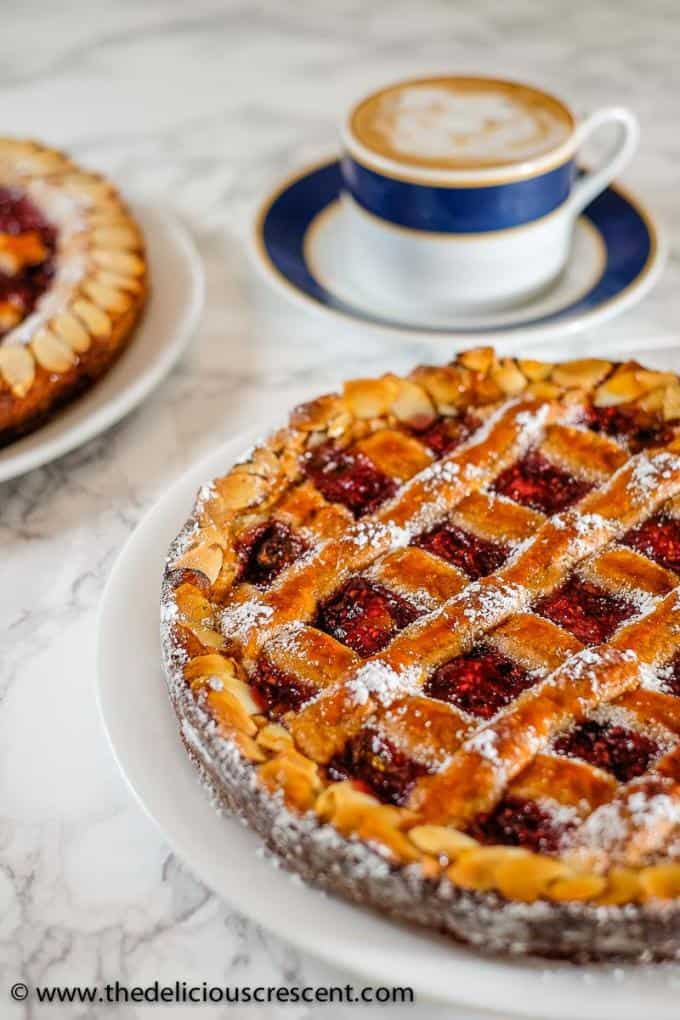Linzer torte placed on a white plate with a cup of coffee on the side.