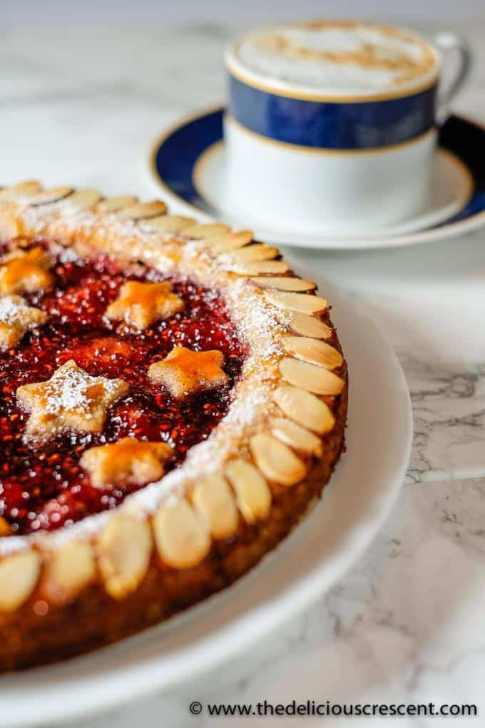 Front view of a decorated Linzer torte with raspberry jam filling.