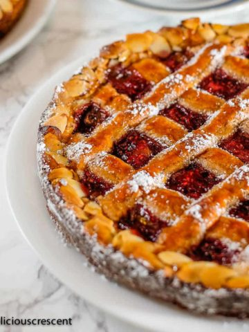 Linzer torte with raspberry filling served with a cup of coffee.
