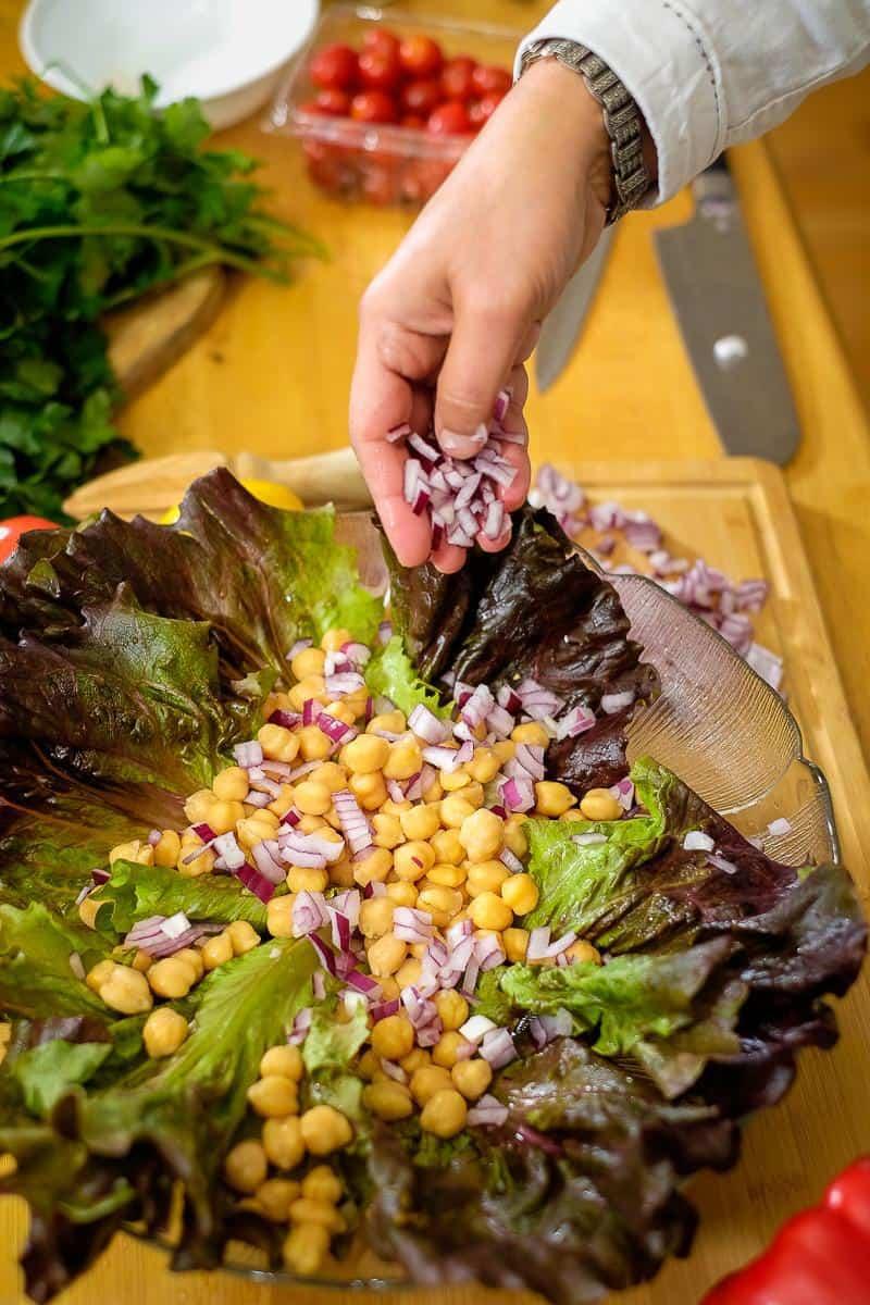 Adding chopped onions to a salad.