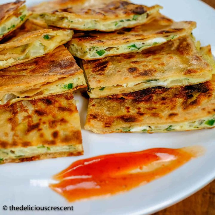 Egg paratha stuffed with omelette mixture, cut into pieces and served on a plate.