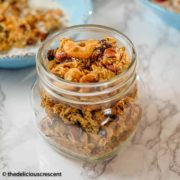 Homemade granola with cashews and cardamom stored in a glass bottle.
