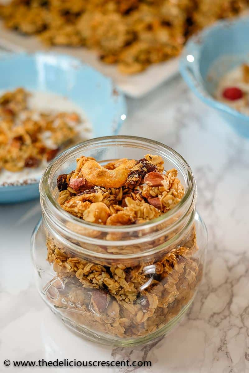 Homemade granola with cashews and cardamom filled in a glass bottle.
