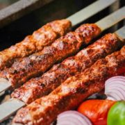 Persian kabob koobideh arranged over flat breads along with grilled vegetables.