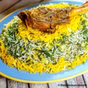 Baghali polo (dill rice with lima beans) served with a lamb shank on a plate.