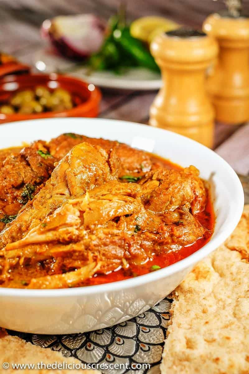 Authentic Indian chicken korma served in a white dish and placed on a table with naan on the side.