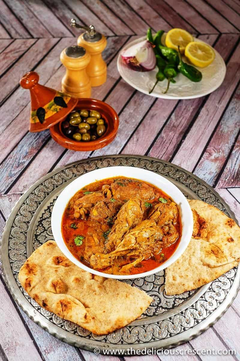 Overhead view of chicken cooked in a fragrant spiced yogurt sauce and served with naan.