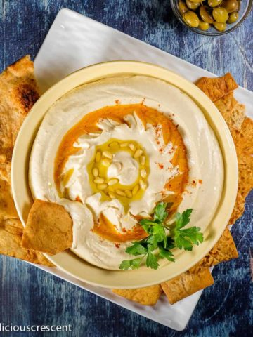 Hummus served in a bowl along with pita chips.