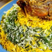 Baghali polo or Persian dill rice, a fragrant fluffy rice dish with pleasant flavors of dill, basmati rice and saffron with plump soft broad beans on a serving platter.