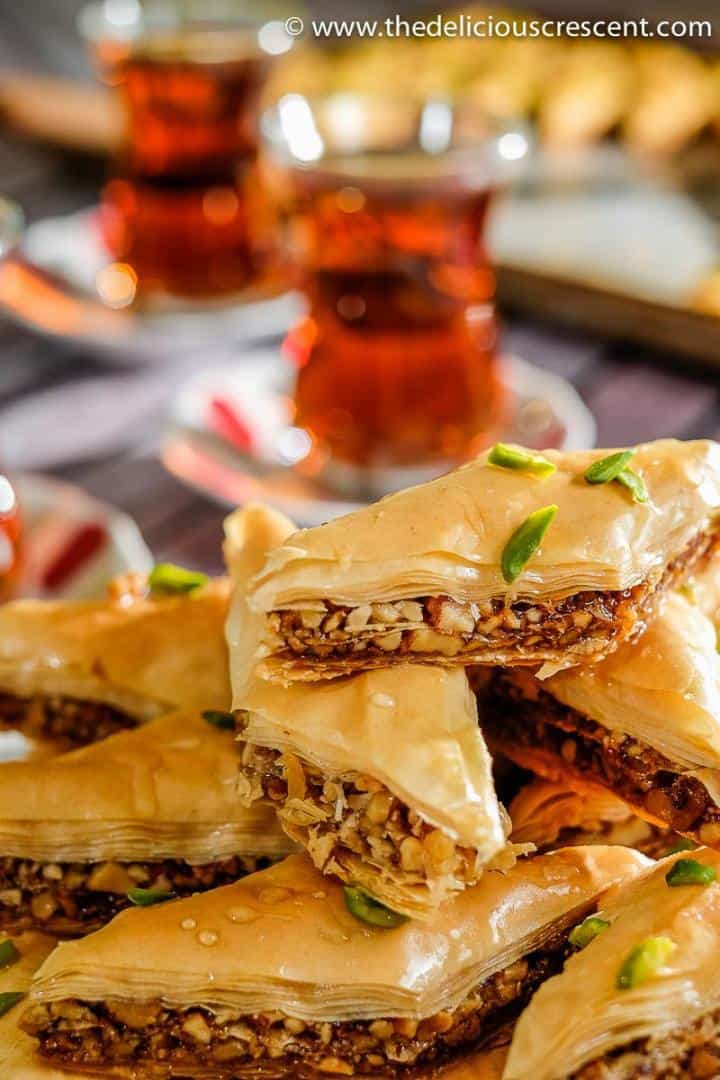 A stack of baklava pieces served with tea.
