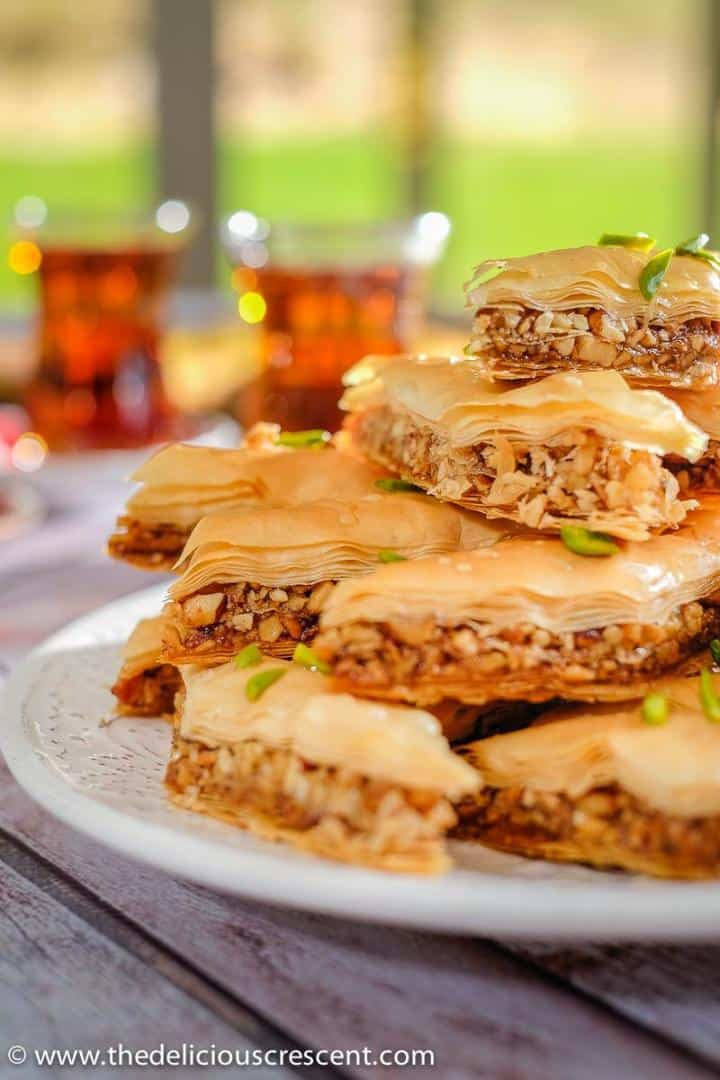Baklava made with walnuts, almonds and honey served on a white plate with two cups of black tea.
