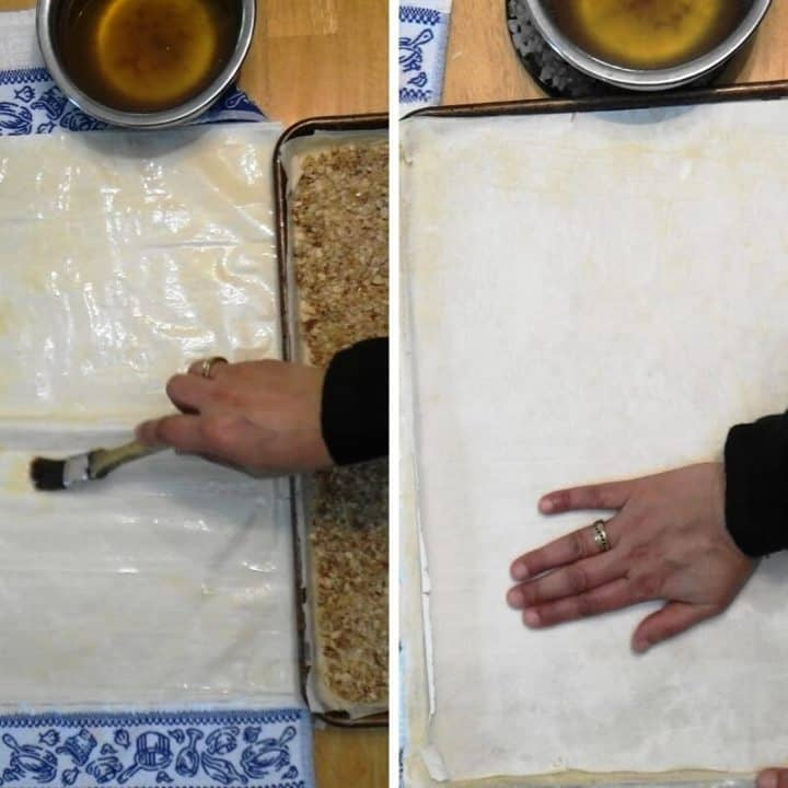 A phyllo sheet being brushed with butter and placed over the nut layer and then gently pressed.