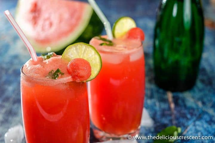 Two glasses of watermelon juice with the fruit in the background.