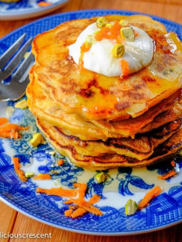 Carrot pancakes stacked and served on a plate.