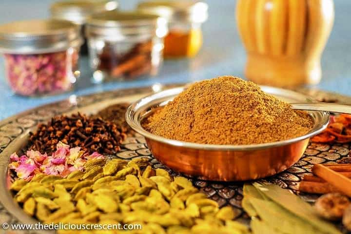 A bowl of ground garam masala with spices placed around it on a plate.