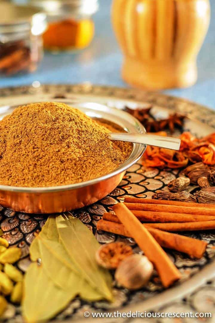 Homemade garam masala filled in a small bowl and placed on a decorative platter with spices.