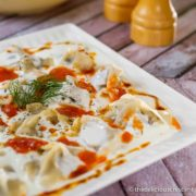 Vegetarian manti dumplings covered with yogurt sauce.
