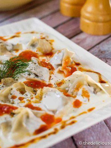 Vegetarian manti dumplings covered with yogurt sauce.