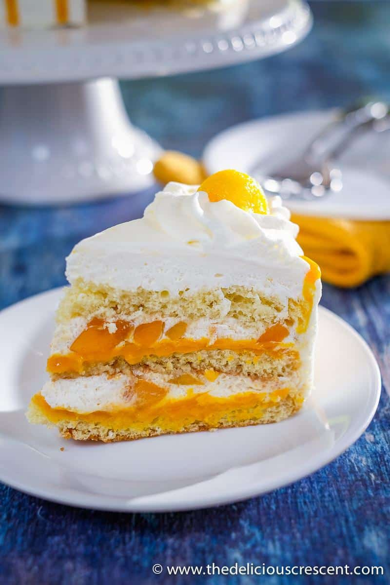 A cake wedge with mango and whipped cream.