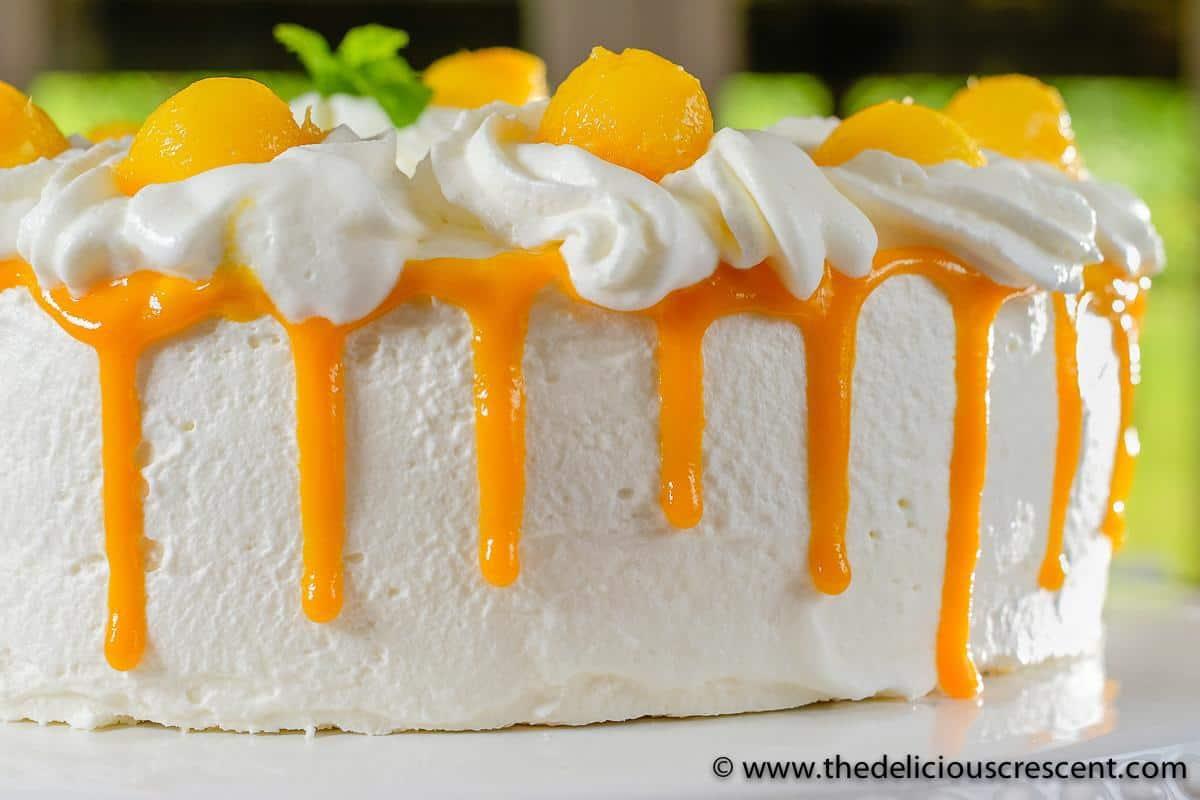 Whipped cream cake showing the mango puree drip decoration.