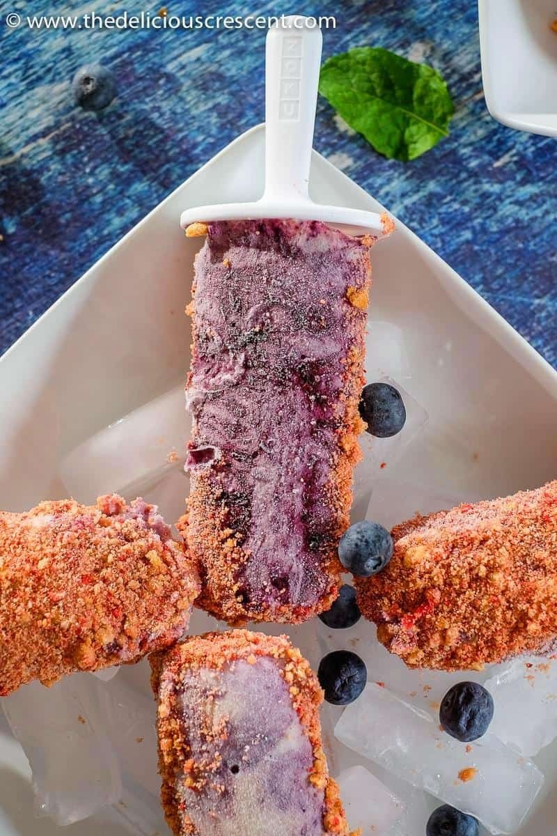 Berry popsicles placed over a plate.