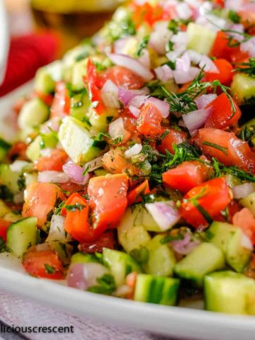 Persian tomato cucumber salad with fresh herbs served on a plate.