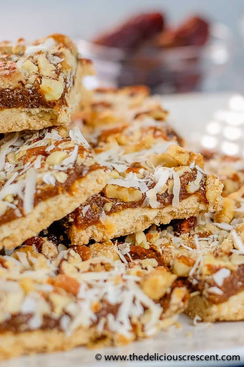 Shortbread crust cookies with a dried fruit filling on top with nuts.