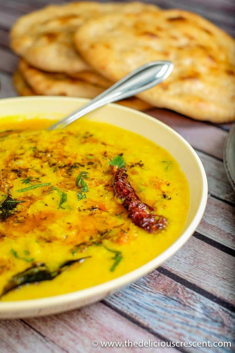 Side view of masoor dal in a bowl with naan.