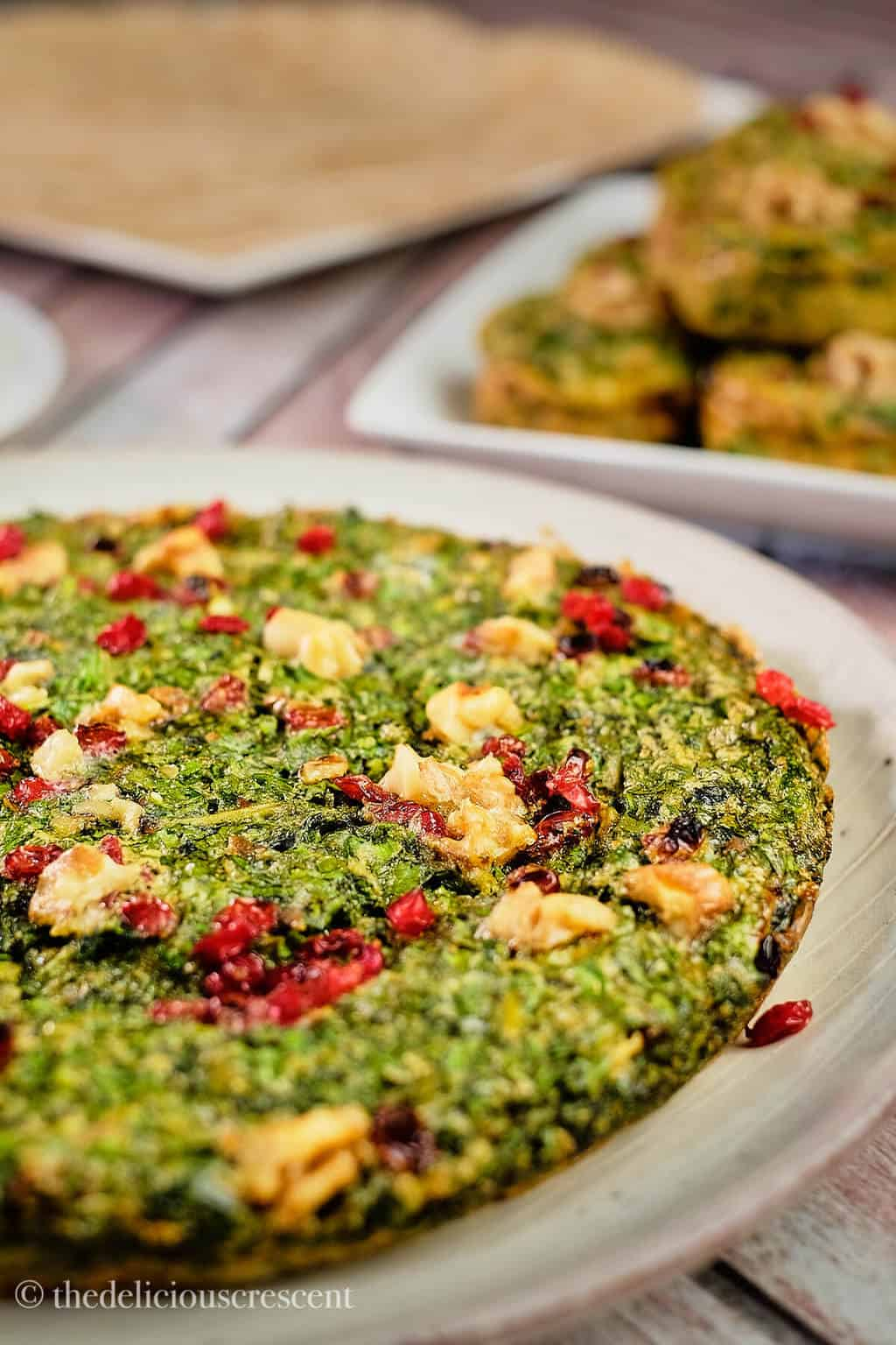 Persian herb frittata served on a plate and placed on a table.